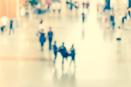 Top view motion blurred passengers in an Asian airport background. Abstract blur crowed of travelers with luggage walking along the hallway corridor. Stock Photo