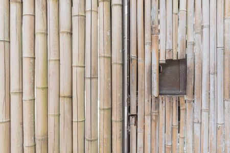 Natural border wall made from bamboo sticks with a hole windows Stock Photo