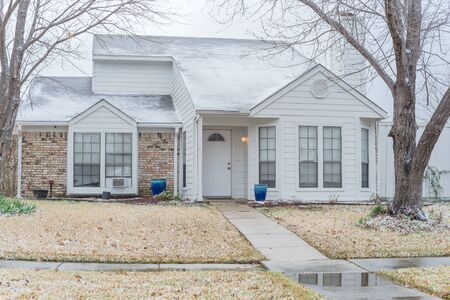 Typical bungalow house under winter snow cover near Dallas, Texas. Middle class residential home in America.