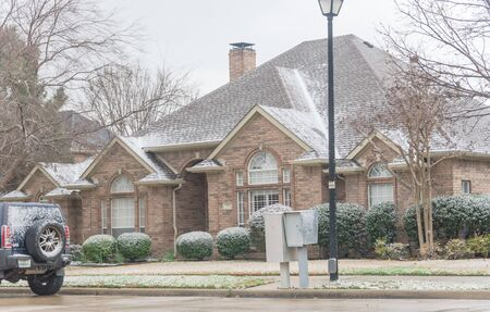 Residential street with typical bungalow house and parked cars under winter snow cover near Dallas, Texas. Middle class residential home in America. Stockfoto