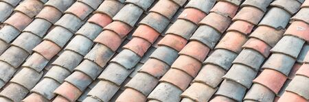 Panorama curved clay tiled roof in various colors from an old house in North Vietnam, late afternoon light. Ancient, weathered roofing surface, moss texture. Natural seamless pattern background