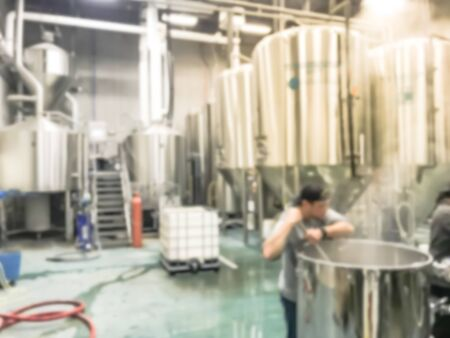 Motion blurred adult brewery workers with cap stirring beer in container while working at local brewing company in North Dallas, Texas, America. Spent grain at brew house Reklamní fotografie