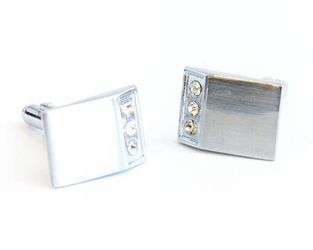 Close-up single pair of modern stainless steel cufflinks isolated on white background. Lifestyle trendy clothing accessories dress with clipping path and copy space.