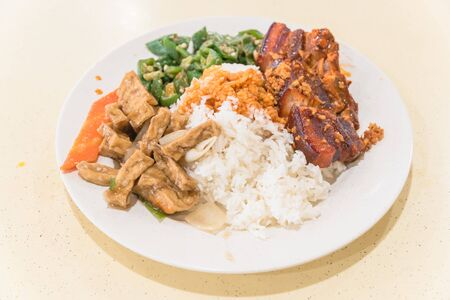 A delicious plate with rice, traditional Chinese braised streaky belly pork, tofu, vegetable and curry sauce at hawker centre of Singapore. Cooked food severed on marble table background.