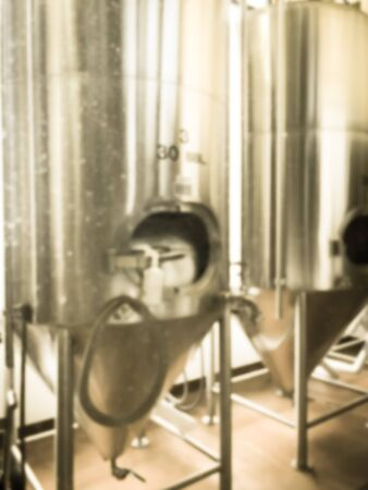 Vintage tone blurred image a full working brewery hops of local restaurant near Dallas, Texas. Row of shiny tanks fermented of standard beer styles and seasonal brews Imagens