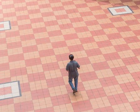 Top view Asian person walking on patio tiles outdoor in Singapore during sunny summer day. Bird eye view people walking over tile pattern background