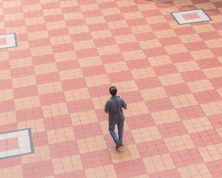 Vue de dessus Personne asiatique marchant sur des carreaux de patio en plein air à Singapour pendant les journées d'été ensoleillées. Vue à vol d'oiseau personnes marchant sur fond de carreaux