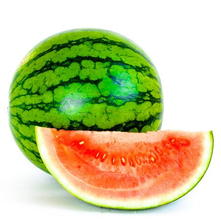 A whole organic mini watermelon with long slice cut isolated on white background.