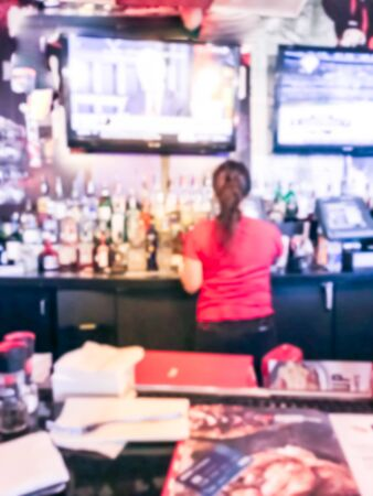 Motion blurred female bartender in red shirt uniform at bar counter of restaurant in Seattle, Washington, USA. Wide variety of alcohol drinks and hanging flat screens, sport bar Zdjęcie Seryjne