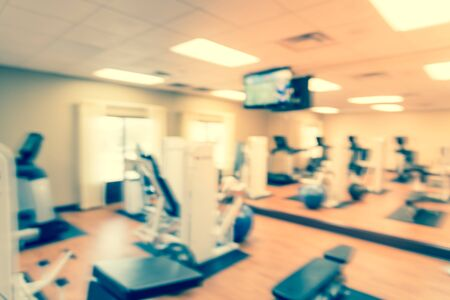 Motion blurred fitness center with medical ball and cardio machines, weight, strength training equipment, large mirror. Empty gymnasium facility service room in hotel Texas, US. Active lifestyle