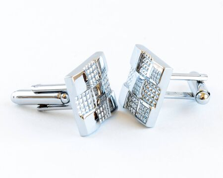 Close-up single pair of modern stainless steel cufflinks isolated on white background. Lifestyle trendy clothing accessories dress with clipping path and copy space. Stock Photo
