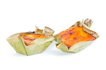 Two mini Bibingka, traditional Philippines cakes isolated on white background. A Filipino baked rice with butter and cheese in banana leaves, usually eaten for breakfast, especially during Christmas season