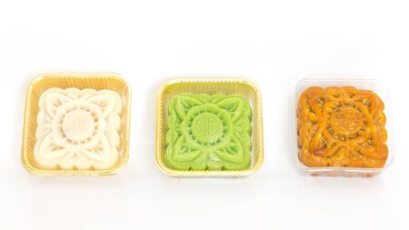 Arrangement of moon cake, snowskin custard (Banh Deo), matcha green tea cake in clear plastic tray isolated on white background. Vietnamese mid-autumn traditional greeting food, copy space Standard-Bild