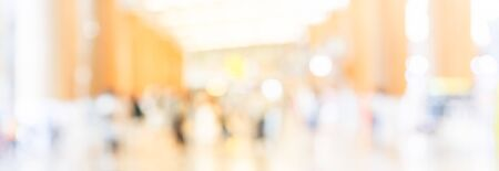 Panorama view abstract blurred passengers in an Asian airport background. Motion blur crowed of people walking along the hallway with natural light from skylight roof windows. Stock Photo