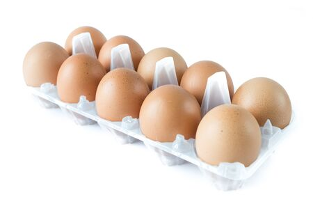 Ten of organic brown eggs on plastic egg carton isolated on white background.