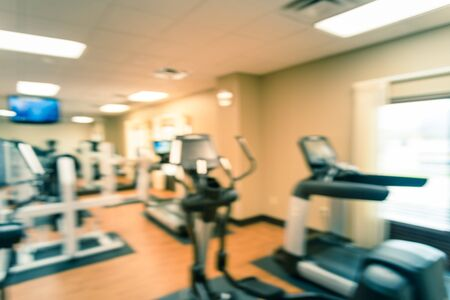 Toned photo blurred fitness center with cardio machines, weight, strength training equipment, TV and large mirror. Empty gymnasium facility service room in 3-star hotel in Texas, US. Active lifestyle
