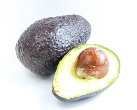 Close-up whole and half cut of avocado isolated on white background. Ripe organic Persea Americana, healthy fat fruits