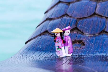 Close-up a couple handicraft magnetic wooden puppets in Vietnamese traditional costumes. Famous Vietnamese dolls souvenirs in natural set with boat and ocean background. Selective focus Imagens