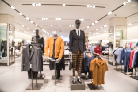 Blurred image of mannequins inside a men fashion store. Abstract blurred of shopping mall boutique interior, men clothes shop with bokeh light background. Imagens