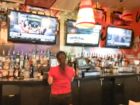 Motion blurred female bartender in red shirt uniform at bar counter of restaurant in Seattle, Washington, USA. Wide variety of alcohol drinks and hanging flat screens, sport bar Imagens