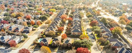 New development neighborhood near Dallas, Texas with colorful orange autumn leaves. Row of two story single family dwelling with large backyard, swimming pool, attached garage and wooden fence garden Stock fotó