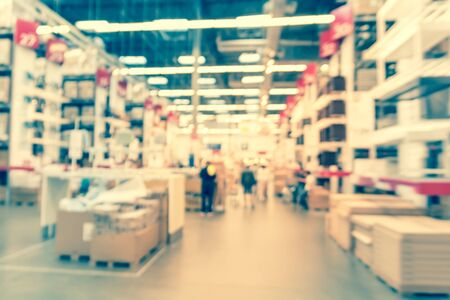 Motion blurred customer shopping in large furniture warehouse in America. Defocused industrial storehouse interior full of boxes, row of aisles, bins, shelves from floor to ceiling