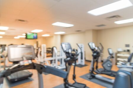 Blurred image of fitness center with cardio machines, weight, strength training equipment, TV and large mirror. Empty gymnasium facility service room in 3-star hotel in Texas, USA. Active lifestyle