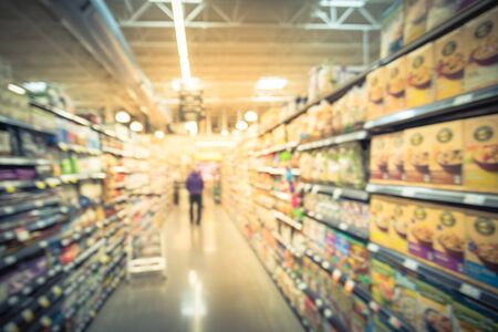 Motion blurred customer shopping for baking supplies, jams, nut butters, coffee, tea, cereals, bars aisle in store at Irving, Texas, US. Supermarket shelves variety of products, defocused bokeh light Imagens