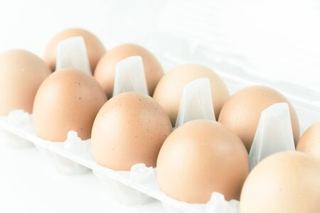 Close-up view of organic Brown Eggs on Plastic Egg Carton isolated on white background. Selective focus and shallow DOF.
