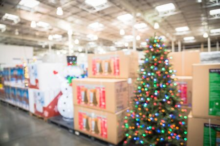 Blurred image pop up led snowman and huge Christmas trees decoration in wholesale store. Wreaths and strings of bokeh light surround the artificial Christmas tree. Xmas cheerful display in America