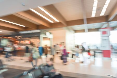 Abstract blurred busy scene at American airport with people walking and waiting for coffee near terminal gate