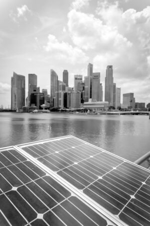 Vintage tone close-up solar panel with modern city and skyscrapers in background in Singapore. Cloud blue sky.