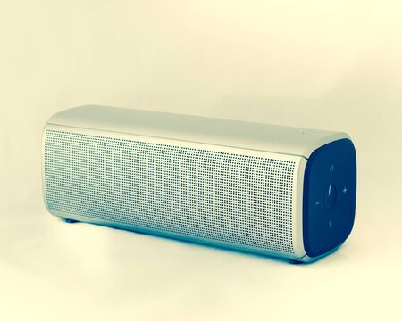 Vintage tone gray wireless speaker with rechargeable batteries isolated on white background. Wireless speaker for digital music listening