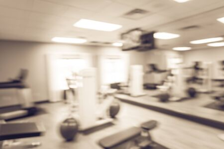 Toned photo blurred fitness center with medical ball and cardio machines, weight, strength training equipment, large mirror. Empty gymnasium facility service room in hotel Texas, US. Active lifestyle