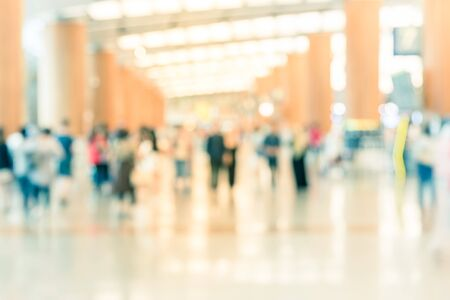 Abstract blurred passengers in an Asian airport background. Motion blur crowed of people walking along the hallway with natural light from skylight roof windows. Imagens