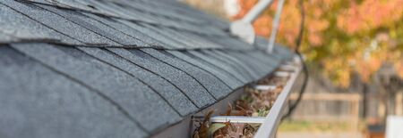Messy gutter near roof shingles with colorful fall foliage and satellite dish in background. Clogged drain pipe full of dried leaves and dirty need to clean-up. Gutter cleaning, home maintenance concept