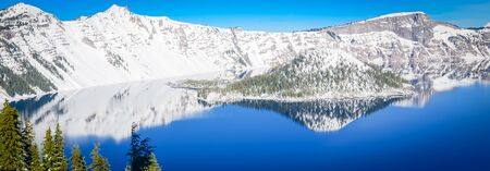 Panorama view pine trees lush cliff above and mirror reflection of snowcap mountain and Wizard Island on Crater Lake, Oregon, USA. Winter scene at Crater Lake National Park volcano