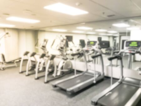 Abstract blurred empty fitness center at modern hotel in Seattle, Washington, US. Row of treadmill, elliptical, strider and workout equipments. Large wall mount mirror and TV.