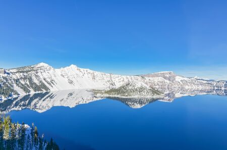 Mirror reflection of snowcap mountain and Wizard Island on Crater Lake, Oregon, USA. Crystal clear blue water and Northwest sky. Winter scene at Crater Lake National Park volcano Imagens