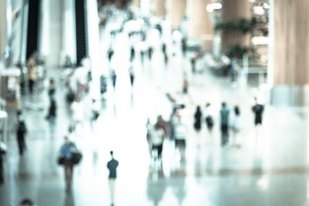 Toned photo top view motion blurred passengers in an Asian airport background. Abstract blur crowed of travelers with luggage walking along the hallway corridor.