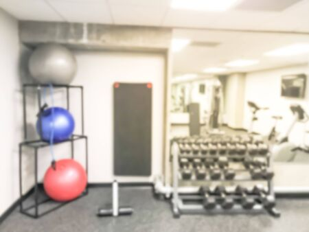 Blurred fitness center at modern hotel in Seattle, Washington, US. Stack of colorful medical ball and row of dumbbell stand, large wall mirror
