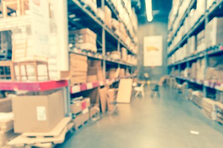 Abstract blurred large furniture warehouse in America. Defocused industrial storehouse interior full of boxes, row of aisles, bins, shelves from floor to ceiling