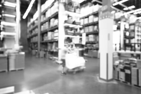 Toned photo blurred customer shopping in large furniture warehouse in America. Defocused industrial storehouse interior full of boxes, row of aisles, bins, shelves from floor to ceiling