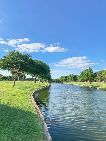 Waterfront subdivision in suburbs Dallas, Texas, USA. Clean river with high stone retaining wall and row of mature oak, bold cypress tree, green grass lawn along the banks. Single family detached home