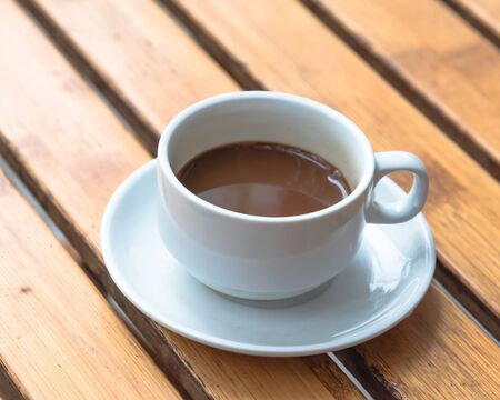 Vietnamese milk coffee in white ceramic cup and saucer on outdoor wooden table. Top view a morning Vietnamese gourmet drink. Food concept.