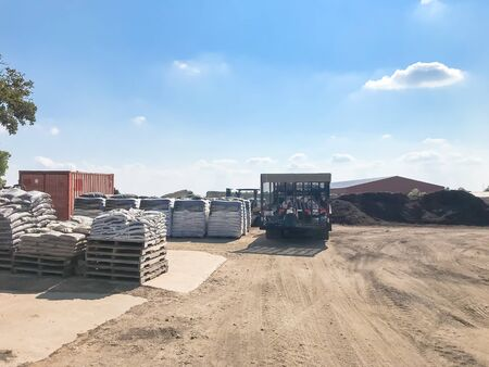Delivery trucks and giant pile of compost, mulch, sand, gravel, soil, stone for bulk sale. Locally sourced and blended organic feed stocks. Landscape, gardening materials wholesaler near Dallas, Texas, USA Archivio Fotografico