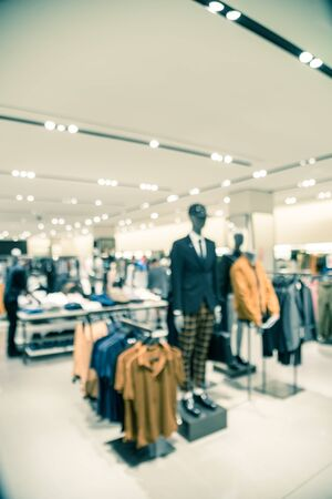 Vintage tone blurred image of mannequins inside a men fashion store. Abstract blurred of shopping mall boutique interior, fall collection men clothes shop with bokeh light background.