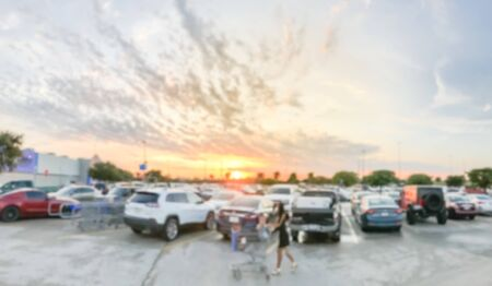 Motion blurred customer with shopping cart walking at parking lots of grocery store near Dallas, Texas, America. Beautiful and dramatic sunset cloud Imagens