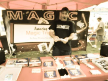 Vintage tone motion blurred magician with mouth speaker showing magic tricks at his booth of local event festival near Dallas, Texas, USA.