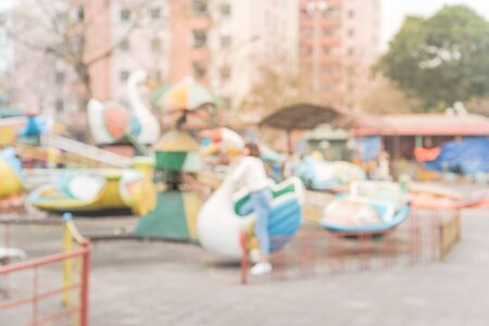 Blurred background playground near apartment building in Hanoi, Vietnam. Colorful amusement style urban recreation with train ride and seesaw.